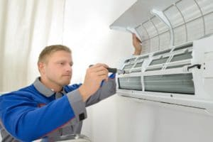 maintenance guy checking split system air conditioner
