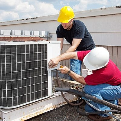 repair men fixing commercial air conditioner