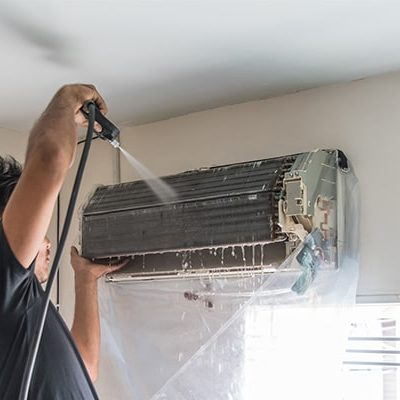 man cleaning split-type aircon with water hose