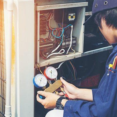 man conducting repair on air conditioning unit